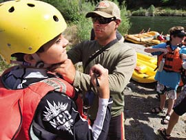 As a Class III river, the Rogue features opportunities for a passenger to fall out around every turn, so safety gear is a must. Before shoving off on the first day, guide Roberto Carrera helps check Alex Brown's helmet and personal flotation device for a proper fit.