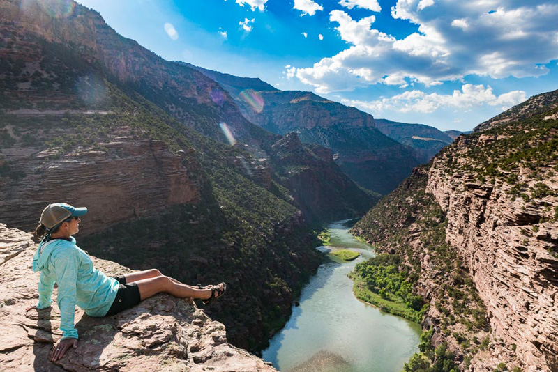 woman sitting on cliff overlooking river