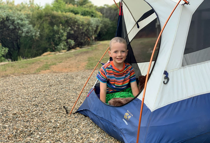 child smiling in tent while camping
